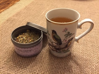 Photo of tea cup filled with herbal comfort hot tea; tin of herbal comfort tea shown